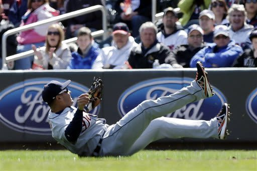 Detroit Tigers' Omar Infante tumbles after falling to field a single hit by Minnesota Twins' Justin Morneau during the first inning of a baseball game, Thursday, April 4, 2013, in Minneapolis. (AP Photo/Jim Mone)