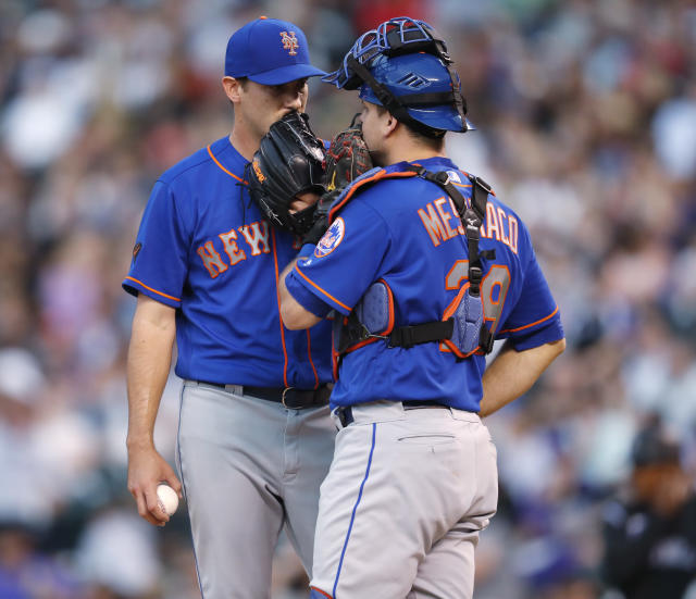 New York Mets starting pitcher Seth Lugo, left, confers with catcher Devin Mesoraco while facing Colorado Rockies' Trevor Story during the third inning of a baseball game Wednesday, June 20, 2018, in Denver. (AP Photo/David Zalubowski)