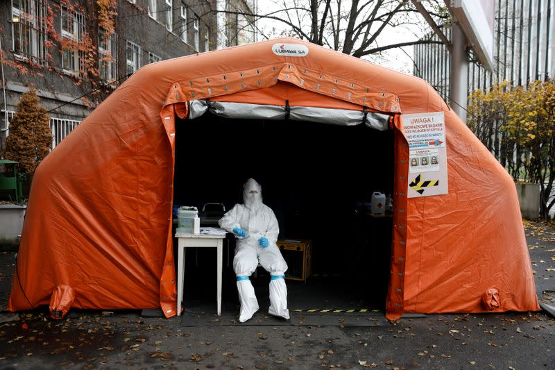 FILE PHOTO: A health worker in protective suit waits for people at a test center in Warsaw