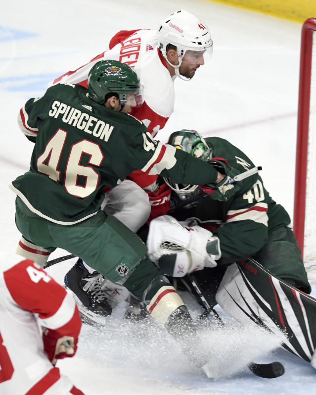 Minnesota Wild's Jared Spurgeon (46) holds off Detroit Red Wings' Luke Glendening, center, as he storms the goal while Wild goalie Devan Dubnyk, right, stops the puck in the first period of an NHL hockey game Saturday, Jan. 12, 2019, in St. Paul, Minn. (AP Photo/Tom Olmscheid)
