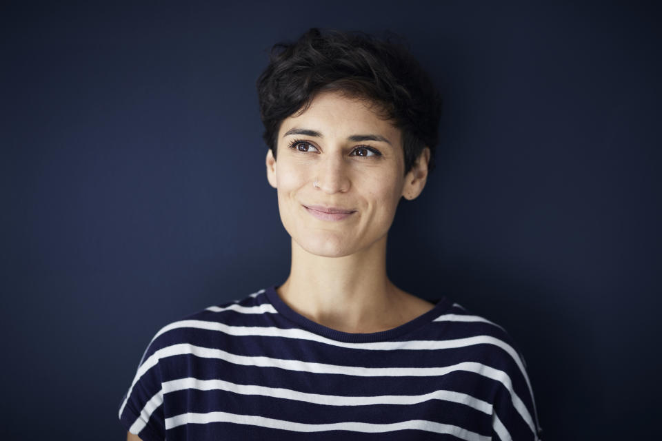 Portrait of smiling woman at blue wall