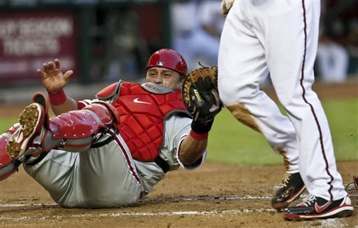 Philadelphia Phillies' Carlos Ruiz, left, dives in vain to tag Arizona Diamondbacks' Paul Goldschmidt who scores a run during the first inning of a baseball game on Friday, May 10, 2013, in Phoenix. (AP Photo/Ross D. Franklin)
