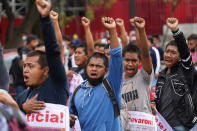 Supporters and relatives of 43 missing university students hold placards with photos of their loved ones as they march on the seventh anniversary of their disappearance, in Mexico City, Sunday, Sept. 26, 2021. Relatives continue to demand justice for the Ayotzinapa students who were allegedly taken from the buses by the local police and handed over to a gang of drug traffickers. (AP Photo/Marco Ugarte)