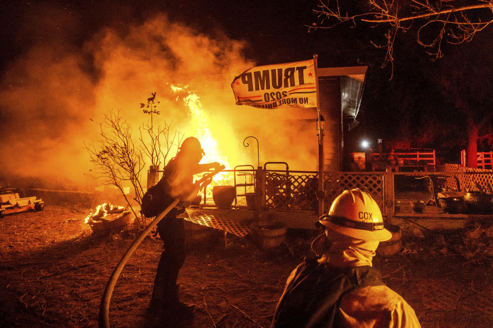 Firefighters spray water on a burning home as the Mountain View Fire tears through the Walker community in Mono County, Calif., on Wednesday, Nov. 18, 2020. (AP Photo/Noah Berger)
