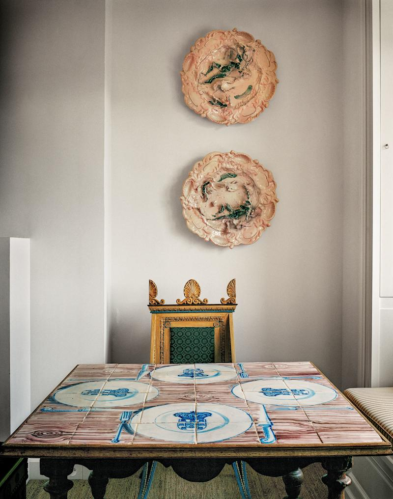 Plates by Lucio Fontana complete a vignette in the master bedroom. 19th-century Neo-Greek chair; table covered with 18th-century Portuguese tiles.