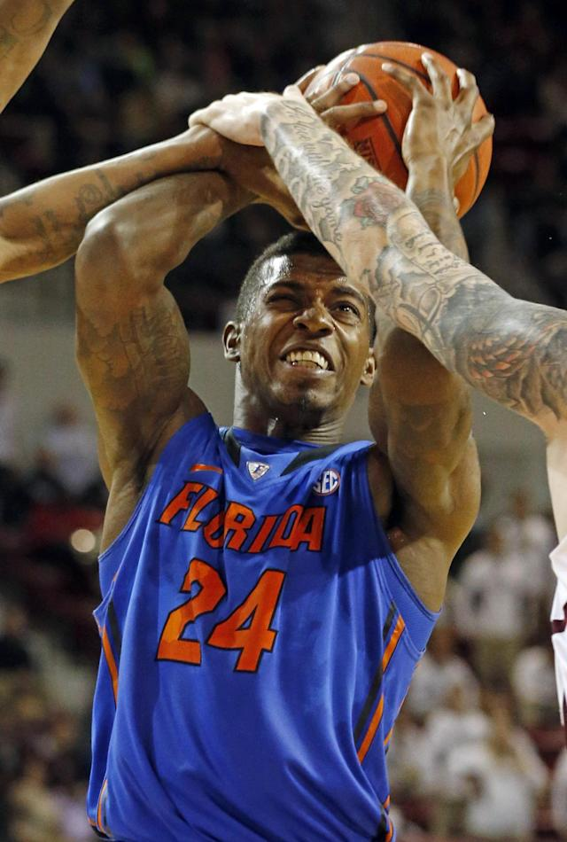 Florida forward Casey Prather (24) is blocked on his shot-attempt by the arms of Mississippi State players Craig Sword, left, and Colin Borchert, right, in the second half of an NCAA college basketball game in Starkville, Miss., Thursday, Jan. 30, 2014. No. 3 Florida won 62-51. (AP Photo)