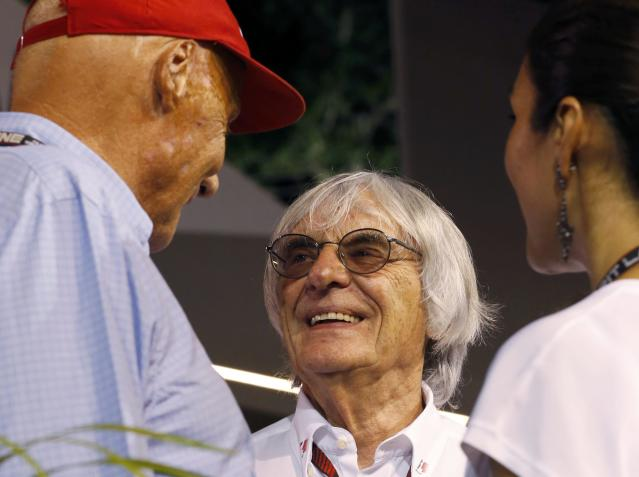 Formula One Chief Executive Bernie Ecclestone (C) talks with former Formula One racing driver and three-time F1 World Champion Niki Lauda of Austria after the qualifying session of the Singapore F1 Grand Prix at the Marina Bay street circuit in Singapore September 21, 2013. REUTERS/Natashia Lee (SINGAPORE - Tags: SPORT MOTORSPORT F1)