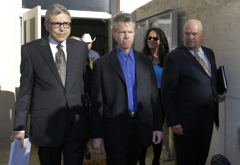 Entertainer Randy Travis, center, exits Grayson County Courthouse with his lawyer Larry Friedman, left, and an unidentified persons, right, Thursday, Jan. 31, 2013, in Sherman, Texas. Travis plead guilty to driving while intoxicated in a plea agreement with the court and will pay a $2,000 fine and serve a two year probation. (AP Photo/Tony Gutierrez)