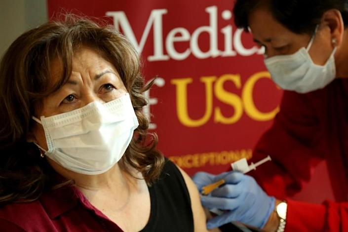 LOS ANGELES, CA - JANUARY 23, 2021 - Nidia Salas, 68, the daughter of Environmental Services Worker Marcos Salas, receives her COVID-19 vaccine from Registered Nurse Mila Tarroza at Keck Medicine of USC in Los Angeles on January 23, 2021. Keck began vaccinating family members, who are 65 and older, of staff that included hospital housekeepers, valet and cafeteria workers. (Genaro Molina / Los Angeles Times)