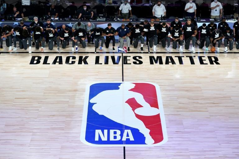 Members of the Utah Jazz and New Orleans Pelicans kneel during the US national anthem as the NBA restarts in Orlando