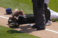 Chicago White Sox's Jose Abreu holds his head after colliding along the first base line with Kansas City Royals' Hunter Dozier in the second inning of the first game of a baseball doubleheader Friday, May 14, 2021, in Chicago. (AP Photo/Charles Rex Arbogast)