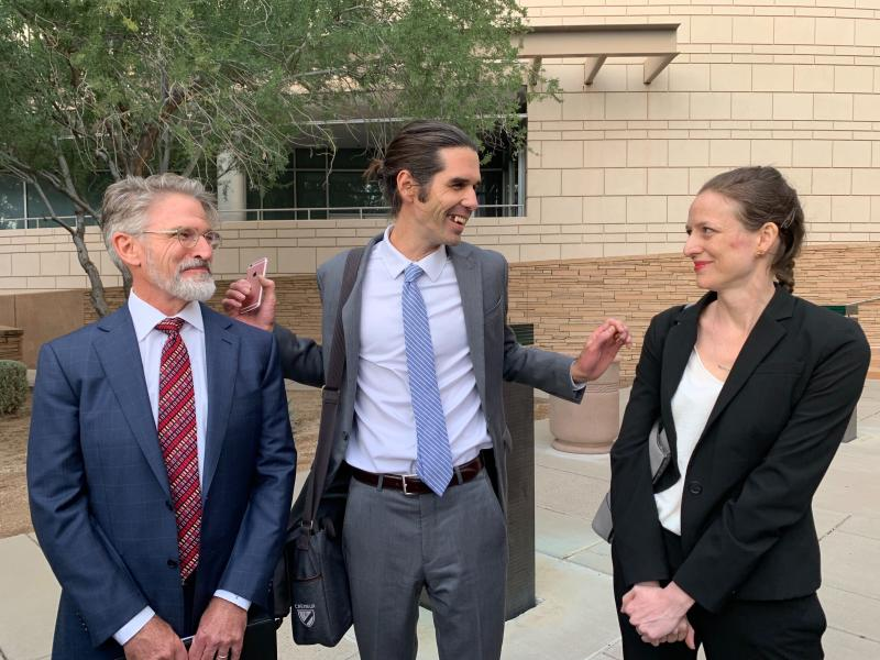 Scott Warren, center, of Ajo, Ariz., celebrates with his attorneys Amy Knight, right, and Greg Kuykendall outside court in Tucson, Ariz. on Wednesday, Nov. 20, 2019, after being acquitted of two counts of harboring in a case that garnered international attention. Prosecutors said Warren illegally helped two migrants avoid authorities. He said he was fulfilling his humanitarian duties by helping two injured men. (AP Photo/Astrid Galvan)