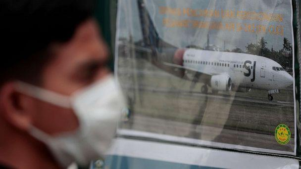 PHOTO: A man walks past a picture of a Sriwijaya Air passenger jet that crashed into the Java Sea put up at the command center for the search and rescue mission at the Port of Tanjung Priok in Jakarta, Indonesia, on Jan. 10, 2021. (Dita Alangkara/AP)