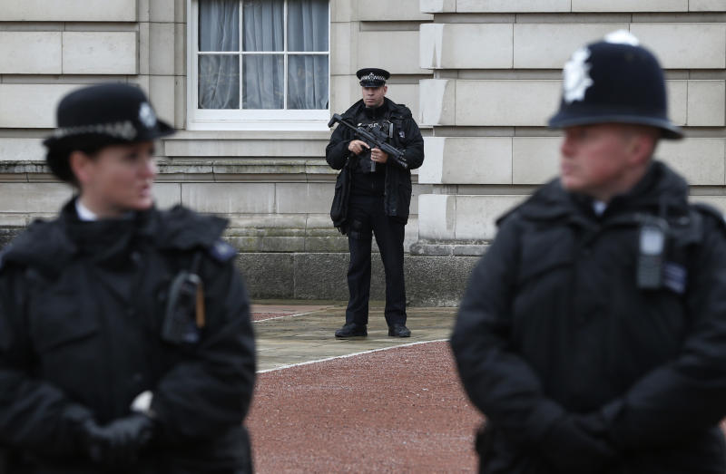 British police officers guard the grounds of Buckingham Palace in central London, Monday, Oct. 14, 2013. British police arrested a man with a knife after he tried to dart through a gate at Buckingham Palace in London on Monday. The palace said Queen Elizabeth II was not in residence. Breaches of royal security are rare, but just a month ago police arrested two men over a suspected break-in at the palace. (AP Photo/Lefteris Pitarakis)