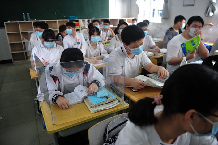 Students read books in the classroom at a high school in Wuhan in central China's Hubei province on July 10, the first day for 10th and 11th grade students to resume school.