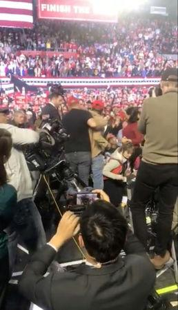 "A man in a ""Make America Great Again"" hat is restrained after he shoved a cameraman during a speech by U.S. President Donald Trump, in El Paso, Texas"