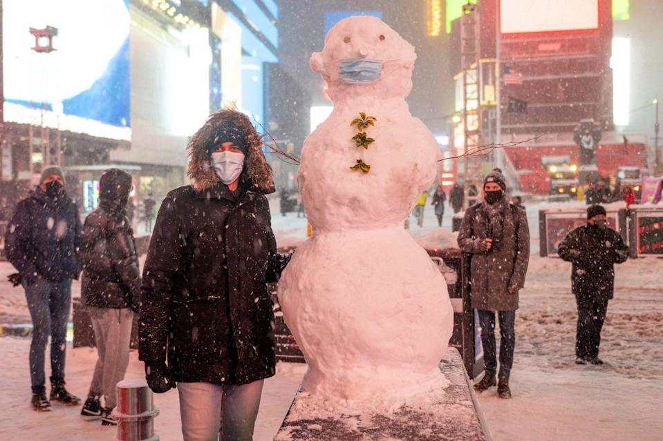 <p>Other Times Square visitors build a snowman — masked, of course.</p>