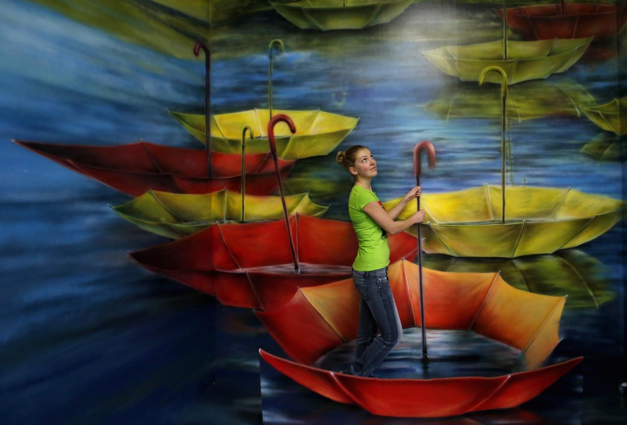 A visitor poses for a photograph at the Museum of Optical Illusions in St. Petersburg October 7, 2014. The museum offers visitors a chance to become involved in their 3D installations, according to local media. REUTERS/Alexander Demianchuk (RUSSIA  - Tags: SOCIETY)