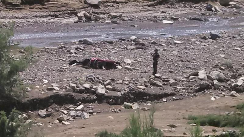 In this Sept 14, 2013 photo, a New Mexico State Police investigator is shown examining a vehicle that authorities believe was washed into a ravine covered in mud near the Elephant Butte dam, killing the motorist. The death is the first related to massive flooding in New Mexico this week from record heavy rains and overflowing rivers. (AP Photo/NM State Police)