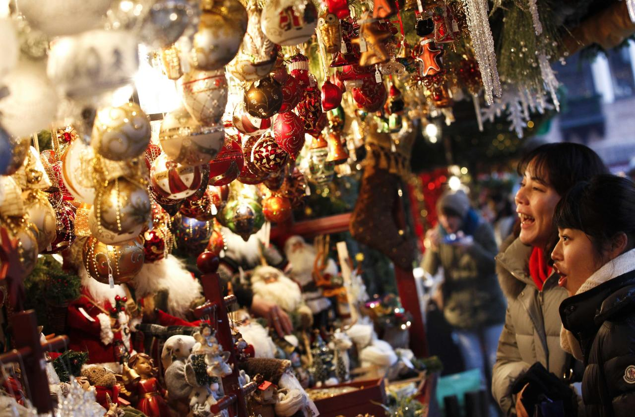 Tourists from Japan look at Christmas decorations on a stall at the opening day of Germany's oldest Christkindlesmarkt (Christ Child Market) in Nuremberg November 29, 2013. The first official record of this pre-Christmas market dates back to 1628. A list of notices for stall holders from 1737 shows that almost all of Nuremberg's craftsmen were represented. Every year, Germany's traditional markets, such as the centuries-old Christkindlesmarkt in medieval Nuremberg, draw millions of visitors, both local and foreign. They open before the first Sunday of Advent and usually continue until December 24 at noon. REUTERS/Michaela Rehle (GERMANY - Tags: SOCIETY ENTERTAINMENT)