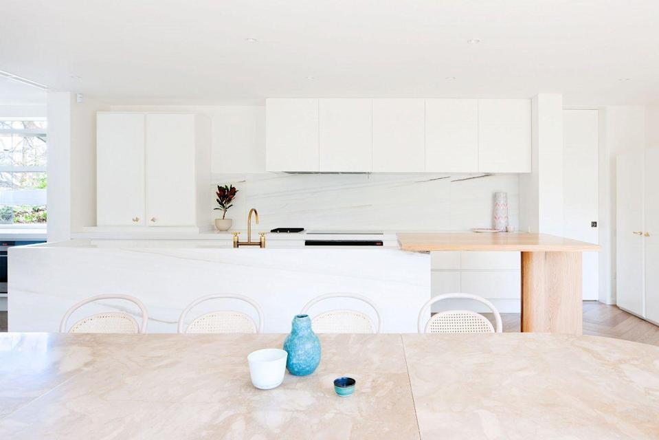 <p>This kitchen by Hecker Guthrie emits a dreamy, romanic rosy glow. Since this home has an open floor plan, the kitchen was designed to blend into a more formal dining and living space while still being functional and livable. The kitchen island is offset with a wood extension, providing a more casual spot to dine. </p>