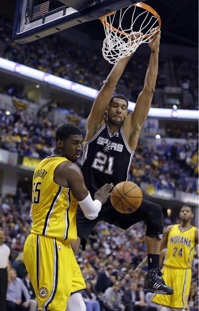 San Antonio Spurs forward Tim Duncan gets a basket on a dunk over Indiana Pacers center Roy Hibbert in the second half of an NBA basketball game in Indianapolis, Monday, March 31, 2014. The Spurs defeated the Pacers 103-77. (AP Photo/Michael Conroy)