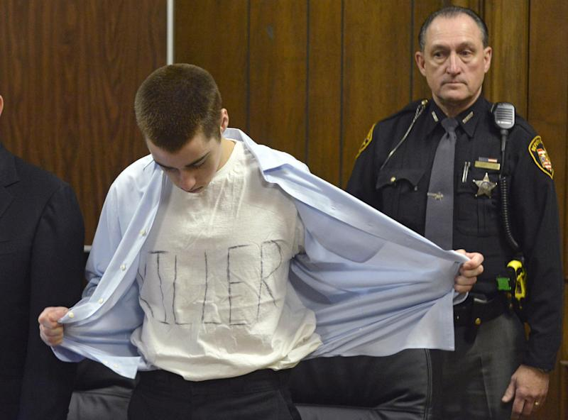 T.J. Lane unbuttons his shirt during sentencing Tuesday, March 19, 2013, in Chardon, Ohio.  Lane, was given three lifetime prison sentences without the possibility of parole Tuesday for opening fire last year in a high school cafeteria in a rampage that left three students dead and three others wounded.  Lane, 18, had pleaded guilty last month to shooting at students in February 2012 at Chardon High School, east of Cleveland. Investigators have said he admitted to the shooting but said he didn't know why he did it. Before the case went to adult court last year, a juvenile court judge ruled that Lane was mentally competent to stand trial despite evidence he suffers from hallucinations, psychosis and fantasies. (AP Photo/The News-Herald, Duncan Scott, Pool)