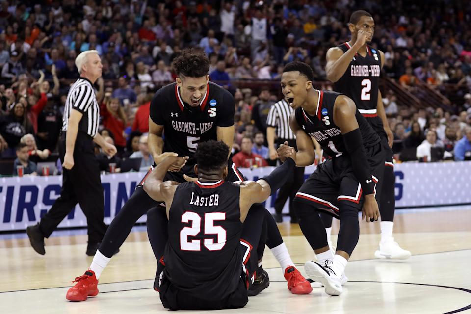 <p>Jose Perez #5 and Jaheam Cornwall #1 of the Gardner Webb Runnin Bulldogs help DJ Laster #25 up after a play in the first half against the Virginia Cavaliers during the first round of the 2019 NCAA Men's Basketball Tournament at Colonial Life Arena on March 22, 2019 in Columbia, South Carolina. (Photo by Streeter Lecka/Getty Images) </p>