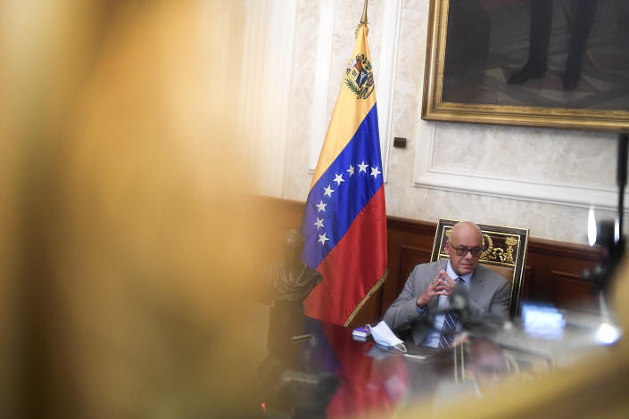 """Reflected in a mirror, National Assembly President Jorge Rodriguez gives an interview at Congress in Caracas, Venezuela, Friday, Jan. 15, 2021. Rodriguez said he's hopeful the Biden administration will roll back a """"cruel"""" sanctions policy and instead give room for diplomacy that could lead to the reopening of the U.S. Embassy and the release of several jailed American citizens. (AP Photo/Matias Delacroix)"""