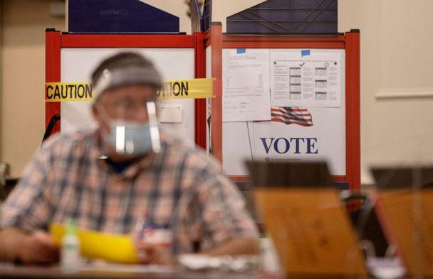 PHOTO: A poll workers sits in front of a voting booth with sides blocked off with caution tape to ensure social distancing at the Italian Heritage Center on July 14, 2020, in Portland, Maine. (Portland Press Herald via Getty Images)