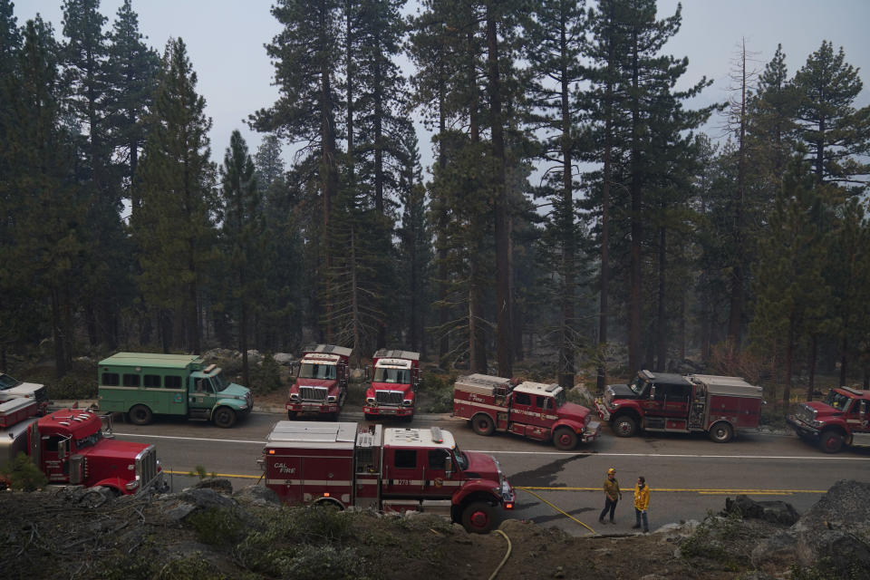 Fire trucks are parked along Highway 89 as fire crews build a fire line to keep the Caldor Fire from spreading in South Lake Tahoe, Calif., Friday, Sept. 3, 2021. Fire crews took advantage of decreasing winds to battle a California wildfire near popular Lake Tahoe and were even able to allow some people back to their homes but dry weather and a weekend warming trend meant the battle was far from over. (AP Photo/Jae C. Hong)