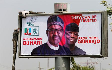 FILE PHOTO: Workers fix an election campaign billboard depicting Nigerian President Muhammadu Buhari and his Vice President, Yemi Osinbajo, in Abuja, Nigeria, January 30, 2019. REUTERS/Afolabi Sotunde/File Photo