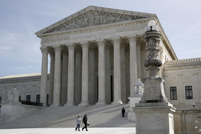 In this March 16, 2020 photo, people walk outside the Supreme Court in Washington.  (AP Photo/Patrick Semansky)