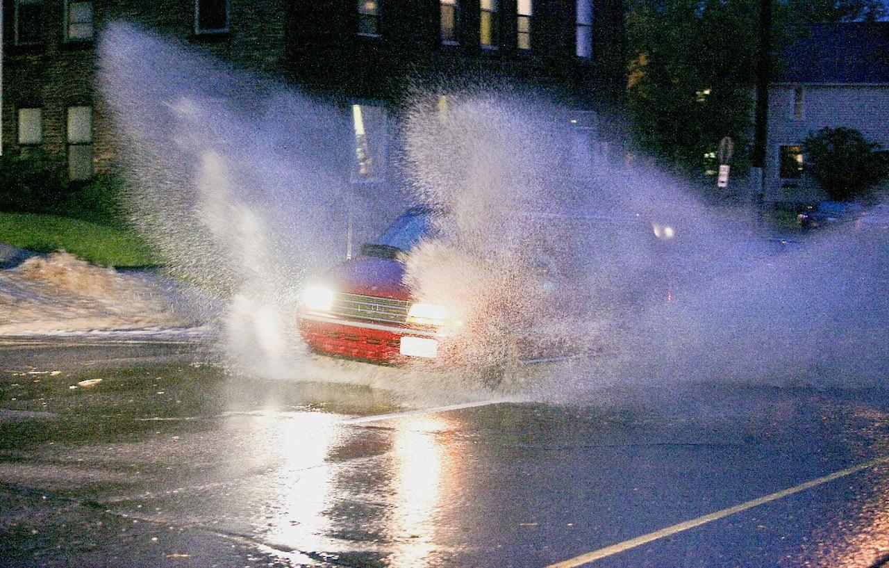 A minivan throws up walls of water while charging through floodwaters in Duluth, Minn., Tuesday, June 19, 2012, after heavy rains hit the area. Floods fed by a steady torrential downpour forced road closures in northeastern Minnesota on Wednesday, and some people were being urged to evacuate their homes because of the rising St. Louis River. Interstate 35 and downtown tunnels in Duluth were closed and police recommended emergency travel only, warning that numerous sinkholes and washouts were making travel dangerous. (AP Photo/The Duluth News-Tribune, Clint Austin)