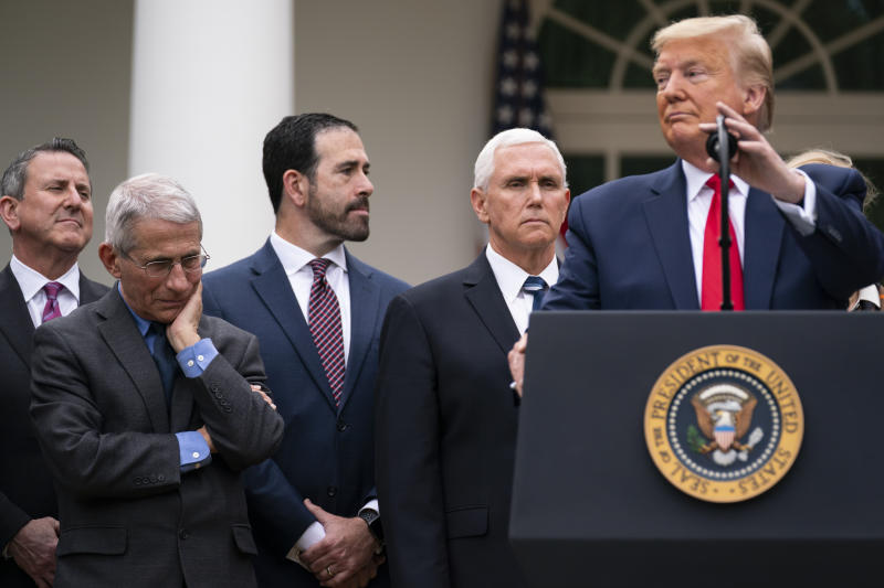 Dr. Anthony Fauci, director of the National Institute of Allergy and Infectious Diseases, listens as President Donald Trump speaks during a news conference on the coronavirus in the Rose Garden at the White House, Friday, March 13, 2020, in Washington. (AP Photo/Evan Vucci)
