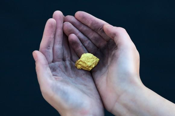 Two hands cradle a gold nugget.