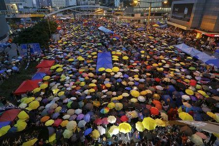 Protesters open their umbrellas, symbols of pro-democracy movement, as they mark exactly one month since they took the streets in Hong Kong's financial central district