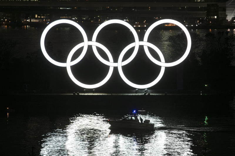 A small boat passes by the illuminated Olympic rings during a ceremony held to celebrate the 6-months-to-go milestone for the Tokyo 2020 Olympics Friday, Jan. 24, 2020, in the Odaiba district of Tokyo. (AP Photo/Jae C. Hong)