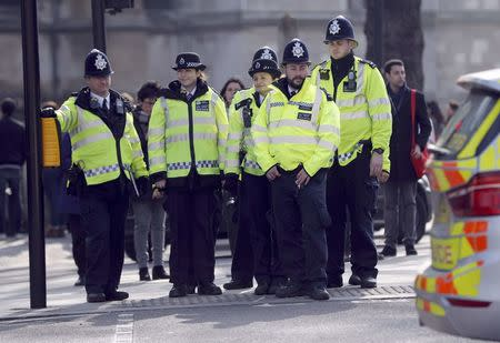 Police officers wait to cross the road outside the Houses of Parliament following a recent attack in Westminster, London, Britain March 24, 2017. REUTERS/Darren Staples