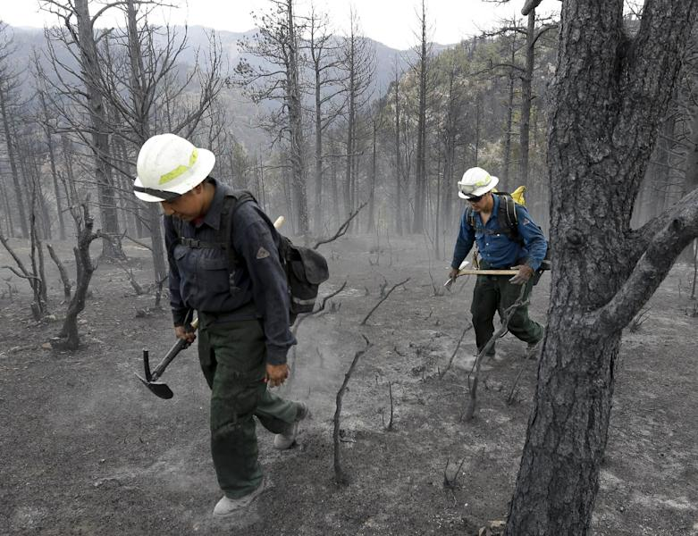 "Members of Bighorn 209, a hand crew from the Crow Agency in Montana check for hot spots on the Waldo Canyon Fire west of Colorado Springs, Colo., Friday, June 29, 2012. After declaring a ""major disaster"" in the state early Friday and promising federal aid, President Barack Obama got a firsthand view of the wildfires and their toll on residential communities. More than 30,000 people have been evacuated in what is now the most destructive wildfire in state history. (AP Photo/Chris Carlson)"