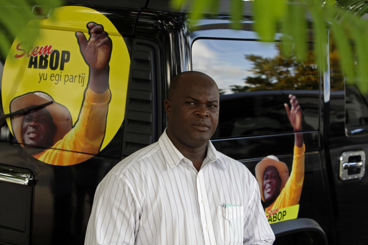 Parliament member Ronnie Brunswijk poses next to his hummer in Paramaribo, Suriname, Tuesday Aug. 10, 2010.  Brunswijk, who in the 1980s led an armed force largely made up descendants of runaway African slaves, known as Maroons, in a civil war against former dictator Desi Bouterse, supported Bouterse's 2010 bid for the presidency.  Bouterse, a former coup leader, convicted drug trafficker and accused murderer will be sworn-in as president of Suriname on Thursday. (AP Photo/Andres Leighton)