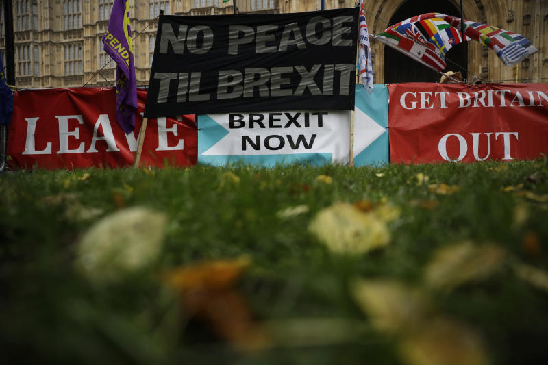 Banners placed by pro-Brexit leave the European Union supporters stand displayed backdropped by the Houses of Parliament in London, Thursday, Oct. 24, 2019. Britain's Prime Minister Boris Johnson won Parliament's backing for his exit deal on Wednesday, but then lost a key vote on its timing, effectively guaranteeing that Brexit won't happen on the scheduled date of Oct. 31. (AP Photo/Matt Dunham)