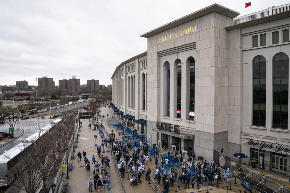 Spectators wait on a security line outside Yankee Stadium before an opening day baseball game against the Toronto Blue Jays, Thursday, April 1, 2021, in the Bronx borough of New York. Fans are back at the ballpark in limited numbers after they were shut out completely during the regular season last year due to the COVID-19 pandemic.(AP Photo/John Minchillo)