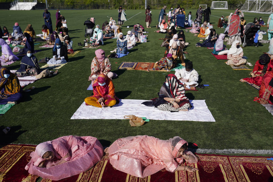 Aqsa Syeda, 8, left front, and her cousin Ameena Ahmed, 9, right front, relax before the start of Eid al-Fitr prayers in Overpeck County Park in Ridgefield Park, N.J., Thursday, May 13, 2021. Millions of Muslims across the world are marking a muted and gloomy holiday of Eid al-Fitr, the end of the fasting month of Ramadan - a usually joyous three-day celebration that has been significantly toned down as coronavirus cases soar. (AP Photo/Seth Wenig)