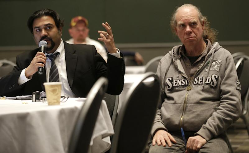 Khurshid Khoja, left, an attorney with San Francisco based Greenbridge Corporate Counsel, asks a question as he sits with marijuana cultivation expert Ed Rosenthal, right, Wednesday, Jan. 30, 2013, in Tacoma, Wash., as they attend an information session put on by Washington's Liquor Control Board for people interested in bidding for consultant contracts with the state to advise on the implementation of legal marijuana use, which was passed into law by voters in 2012. (AP Photo/Ted S. Warren)