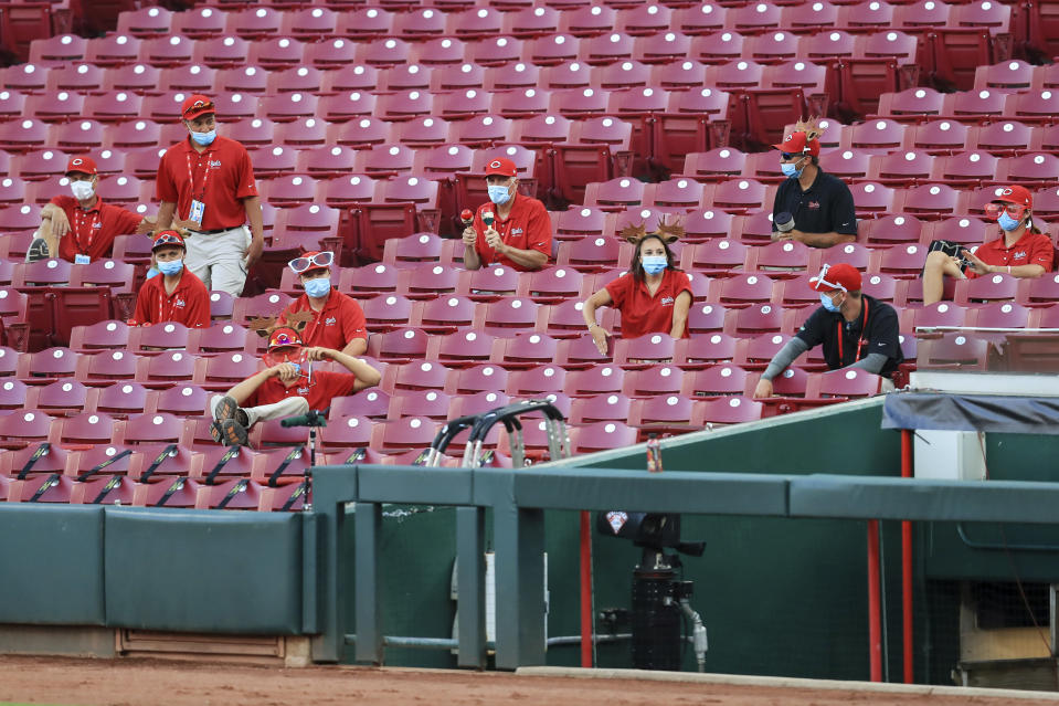 Members of the grounds crew react and make noise from the stands in the fourth inning during a baseball game between the Chicago Cubs and the Cincinnati Reds in Cincinnati, Wednesday, July 29, 2020. (AP Photo/Aaron Doster)