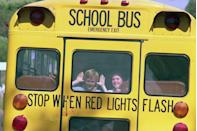 <p>Two students have a bit of fun looking out the back window of their bus on the way home from the first day of school. </p>
