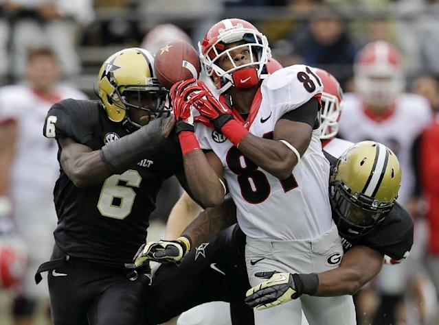 Georgia's Reggie Davis (81) fumbles a punt as he is hit by Vanderbilt defenders Darrius Sims (6) and Jahmel McIntosh, right, in the first quarter of an NCAA college football game on Saturday, Oct. 19, 2013, in Nashville, Tenn. Georgia recovered the ball on the play. (AP Photo/Mark Humphrey)