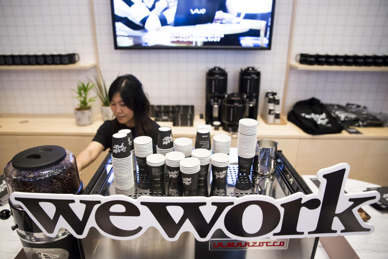 TOKYO, JAPAN - JULY 19: An employee is seen behing the logo of WeWork Companies Inc. during the SoftBank World 2018 conference on July 19, 2018 in Tokyo, Japan. The annual business event hosted by SoftBank, Japan's multinational telecommunications and internet company, takes place for 2 days until July 20. (Photo by Tomohiro Ohsumi/Getty Images)