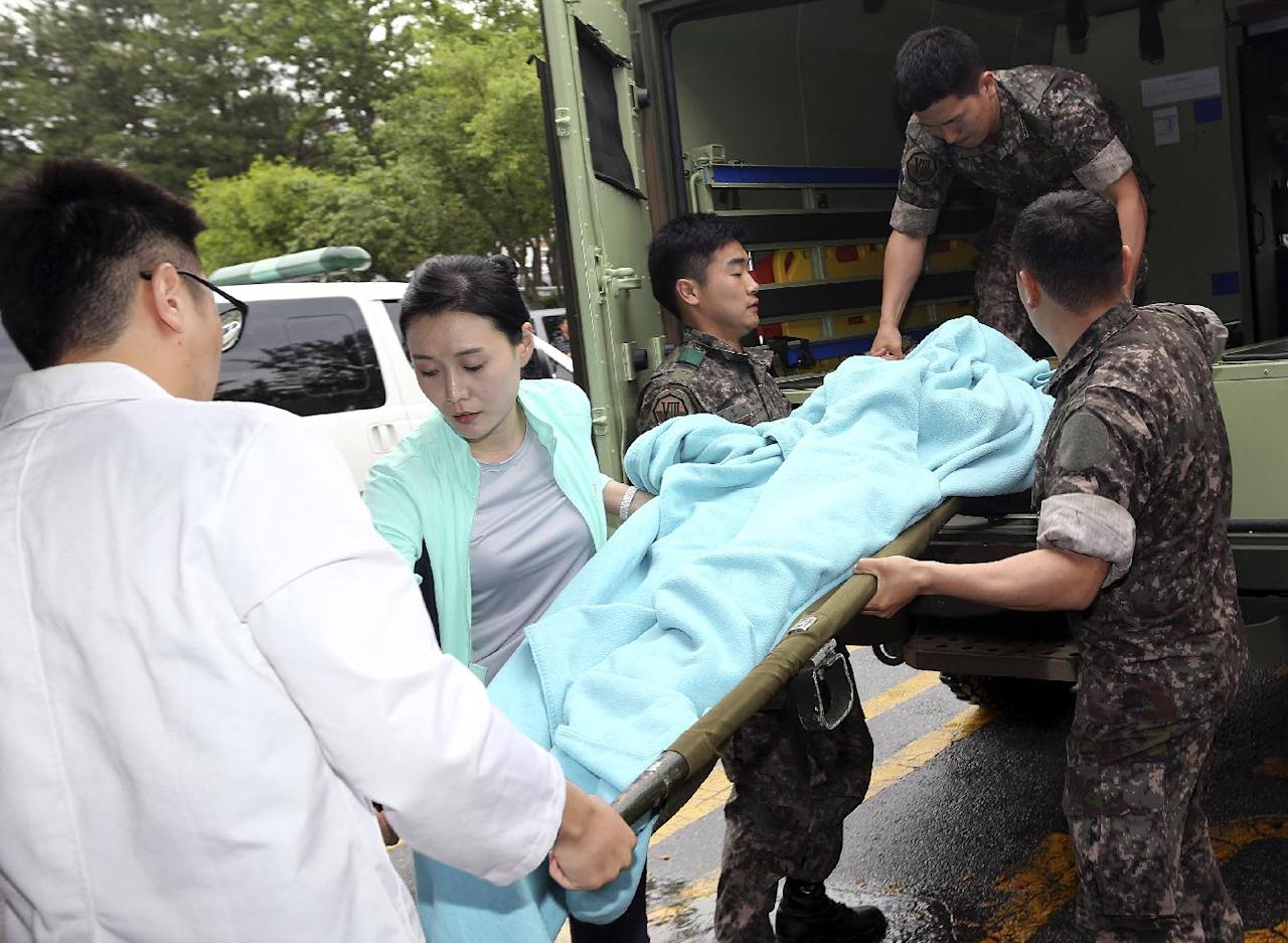 A wounded South Korean soldier who killed five comrades in a shooting incident on a stretcher is carried from an ambulance upon arrival at a hospital in Gangneung, South Korea, Monday, June 23, 2014. The South Korean army captured the soldier Monday who it says killed five comrades and then fled into the forest where he holed up with a rifle for two days before shooting himself as pursuers closed in. The massive manhunt ended when the 22-year-old sergeant, surnamed Yim, shot himself in the upper left chest as his father and brother approached, pleading with him to surrender, a Defense Ministry official said. (AP Photo/Yonhap, Lee Sang-hack) KOREA OUT
